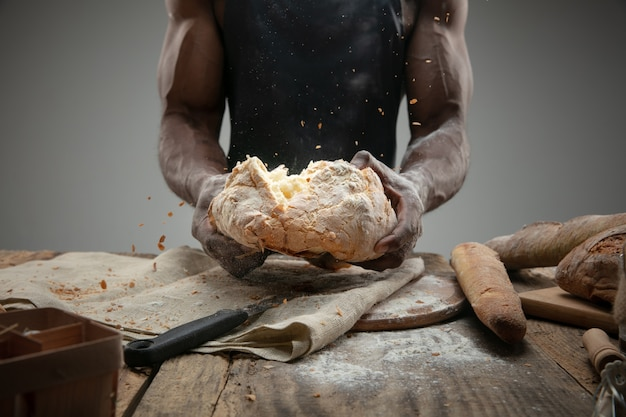 Chiuda in su dell'uomo afro-americano cuochi cereali freschi, pane, crusca sulla tavola di legno. mangiare gustoso, nutrizione, prodotto artigianale