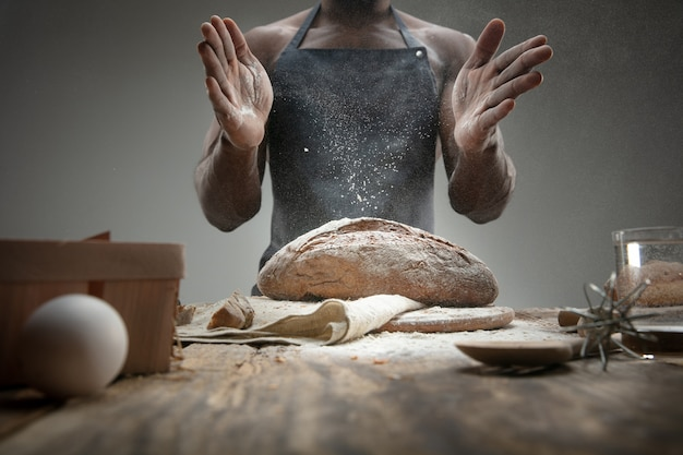 Close up of african-american man cooks fresh cereal, bread, bran on wooden table