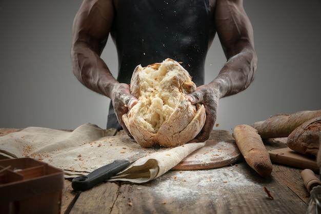 Chiuda in su dell'uomo afro-americano cuochi cereali freschi, pane, crusca sulla tavola di legno