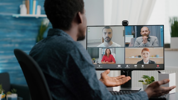 Close up of african american man on online conference video call with his colleagues. computer user working from home in home office chatting using internet distance communication