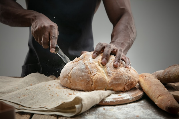 Close up of african-american man slices fresh bread with a kitchen knife