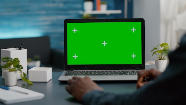Close up of african american man using green screen laptop in bright living room
