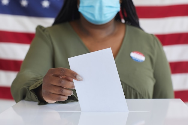 Close up of african-american woman wearing mask putting vote bulletin in ballot box and  while standing against american flag on election day, copy space