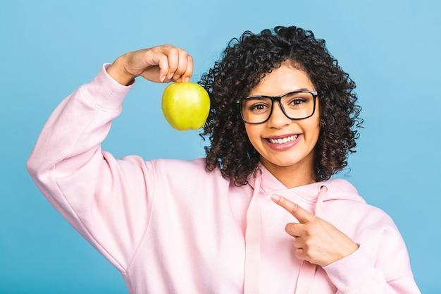 健康的な歯を見せる笑顔を示し、青リンゴを持ち、歯科用ホワイトニングサービス、口腔衛生、治療を推奨する満足しているクライアントの顧客を示すアフリカ系アメリカ人の若い女性をクローズアップ