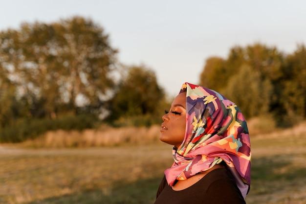 왼쪽을보고 hijab라는 스카프에 weared 아프리카 흑인 여성을 닫습니다