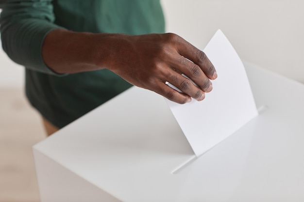 Close-up of african man holding ballot and giving his voice during voting