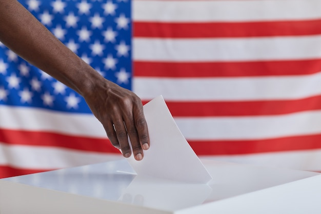 Close-up of african man holding envelope and putting it into the ballot box during voting in america