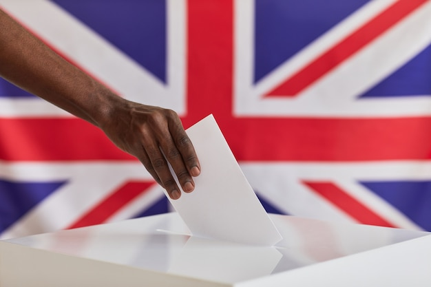 Close-up of african man putting ballot into voting box against the british flag