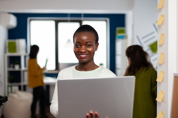 Close up of african woman looking at camera smiling standing in start up creative agency office holding laptop, typing on it