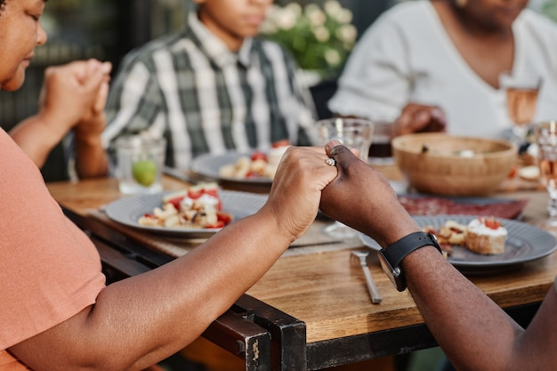 Close up of africanamerican family holding hands at dinner outdoors and praying copy space