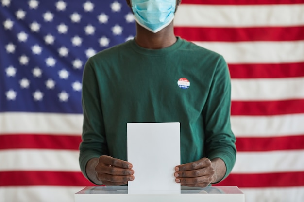 Close-up of afro-american voter in mask holding ballot while standing near the ballot box against the american flag