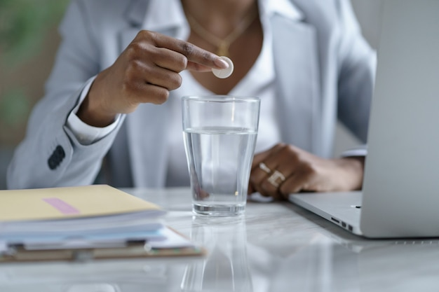 Close up afro business woman dissolves an influenza pill in a glass of water, focus on foreground