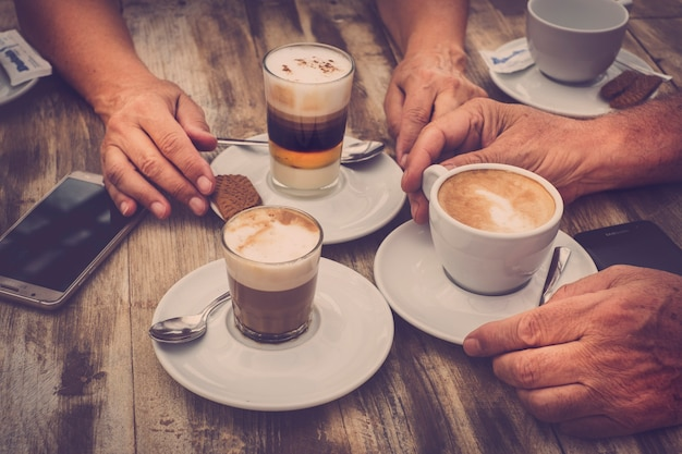 Close up aged caucasian hands with coffee cappuccino at the bar for breakfast - wooden table and vintage romantic color tones - mobile phone with the people - love and couple concept