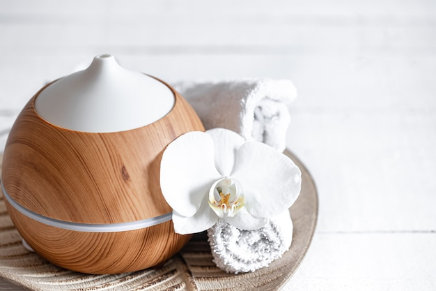 Close up of air humidifier, towel and orchid flower. aromatherapy and care and health concept.