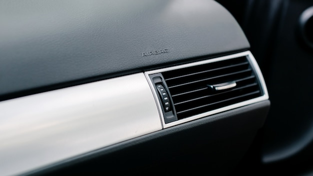 Close-up of air vent in car. airbag icon on the car panel.