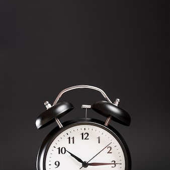 Close-up of a alarm clock against black background