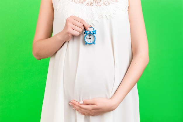 Close up of alarm clock against pregnant womans belly in white dress at green background