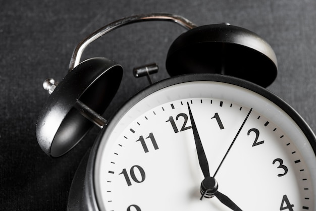 Close-up of a alarm clock on black background