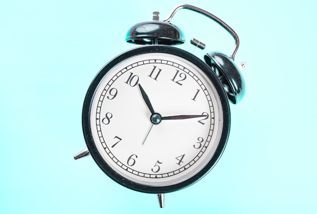 Close up of an alarm clock on blue background