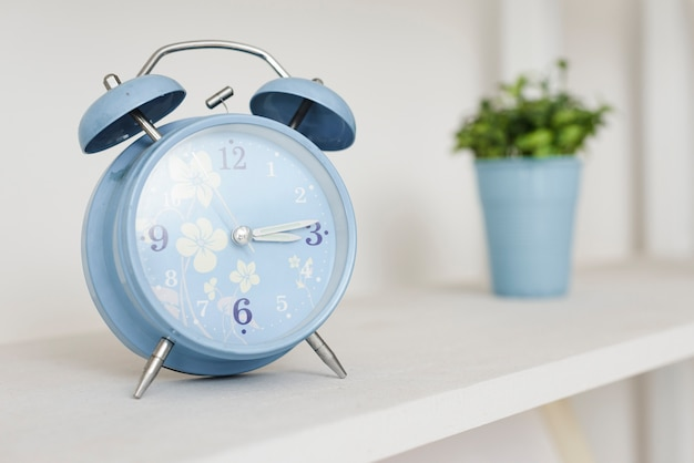 Close-up alarm clock in bookshelf