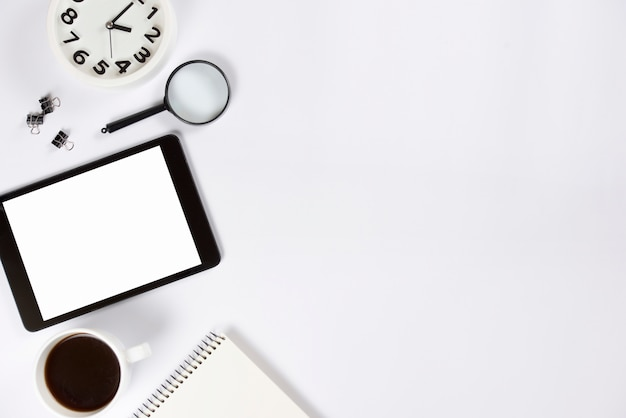 Close-up of alarm clock; magnifying glasses; digital tablet; coffee cup and spiral notepad on white background