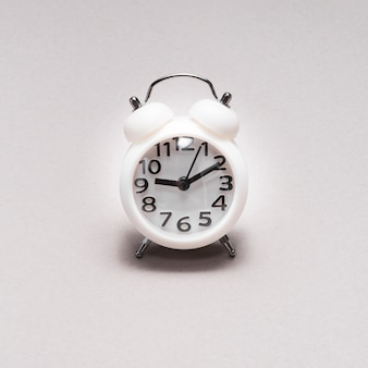 Close-up of an alarm clock on plain background
