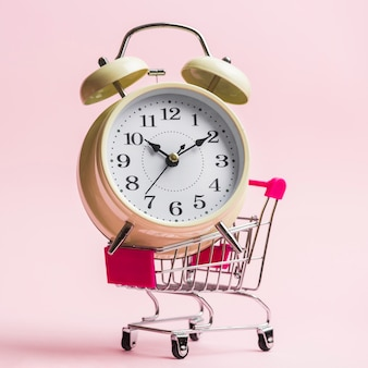 Close-up of an alarm clock on trolley over pink background