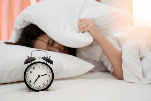 Close up alarm clock with young asian woman lazy waking up in early morning for routine daily job.