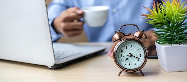 Close up alarm clock with young businessman using laptop