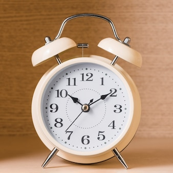 Close-up of an alarm clock on wooden background