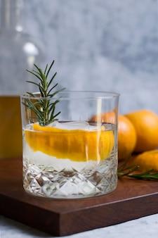 Крупный план алкогольного напитка с розмарином и апельсином