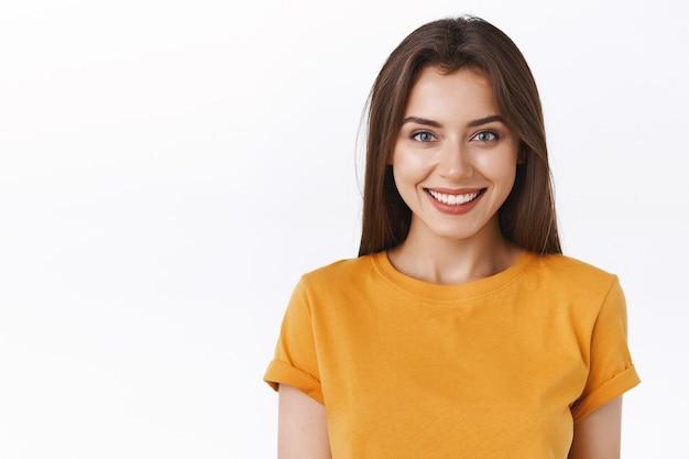 Крупный план заманчивой счастливой улыбающейся брюнетки в желтой футболке, которая с нетерпением ждет захватывающего события, радостно улыбается, выражает позитив и энтузиазм, рада принять участие в интересной промо-кампании