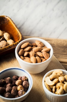 Close-up of almond; hazelnut; cashew nut and peanuts in bowl on chopping board