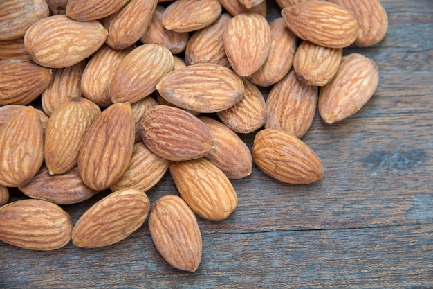 Close up of almonds grain roast on wood background with green leaves