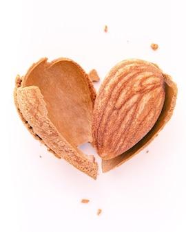 Закройте вверх по скорлупе ореха миндаля треснувшему в форме сердца, изолированному на белой предпосылке. любовь концепции здорового питания.