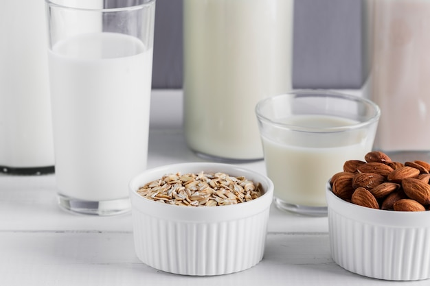 Close up almonds and oatmeal with milk glasses