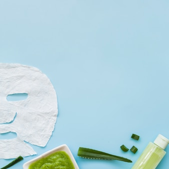 Close-up of aloevera face mask; spray bottle and leaf on blue background