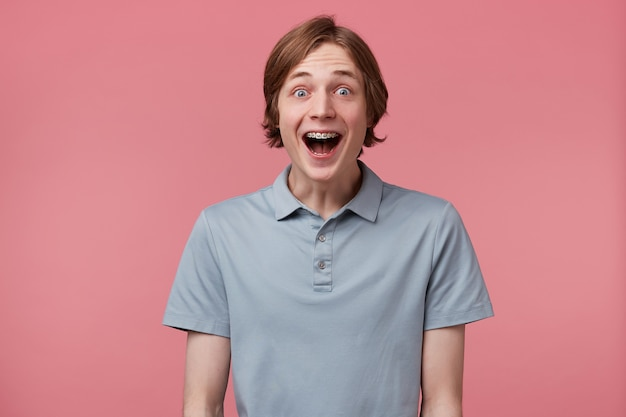 Close up of amazed excited young man with long neatly combed hair and braces on teeth wears polo t-shirt shouting and feels happy surprised isolated over pink background