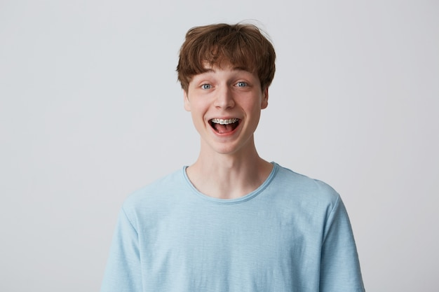 Close up of amazed excited young man with short disheveled hair and braces on teeth