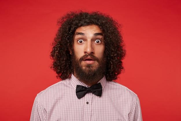 Primo piano del giovane uomo riccio castana stupito con la barba che guarda alla macchina fotografica con gli occhi spalancati e la fronte rugosa, indossa una camicia a scacchi e papillon nero su sfondo rosso