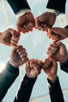 Крупным планом амбициозная бизнес-команда, стоящая в круге