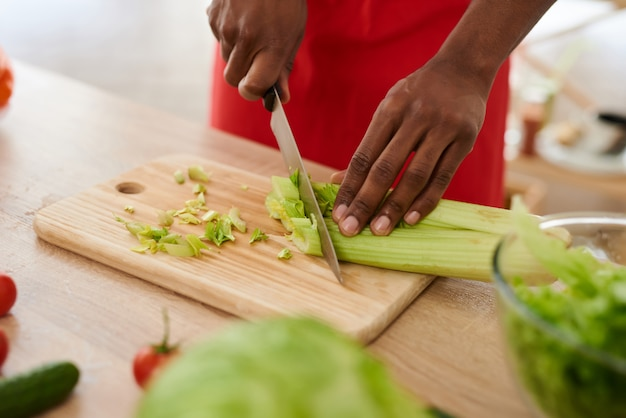 Close up. american man in apron sliced celery in kitchen.