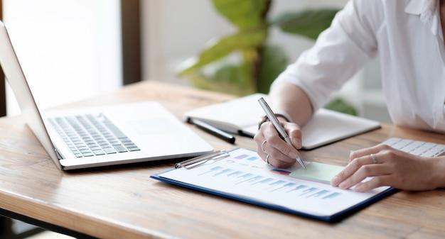 クローズアップ、会計士または事業主は付箋に書き込み、付箋にメモを取り、財務報告に取り組み、事業予算を計算します