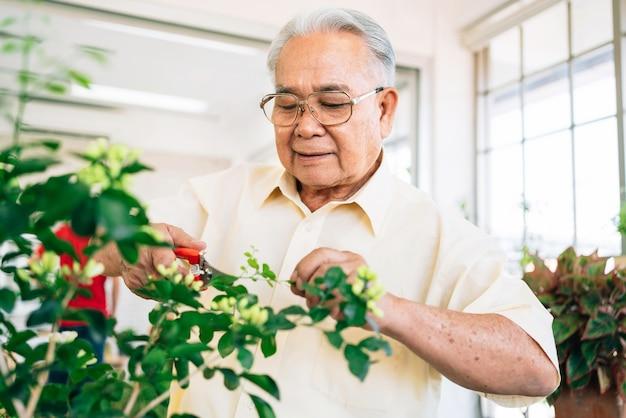 Крупный план дедушка-пенсионер из азии любит с улыбкой и радостью ухаживать за растениями в домашнем саду дома. пенсионная деятельность.