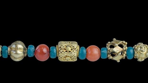 黒の背景にネックレスのターコイズガラスビーズとカーネリアンビーズで区切られた古代の珍しい切望された金のビーズをクローズアップ