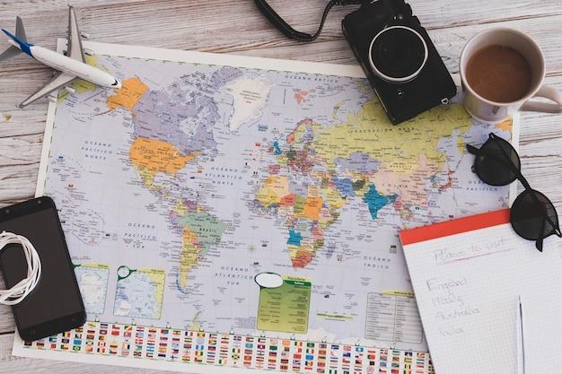 지도와 휴가 및 여행에 대한 내용이 있는 흰색 나무 테이블의 위 및 위쪽 보기를 닫고 초상화 - 휴가 및 라이프스타일과 개념을 떠나는 여행