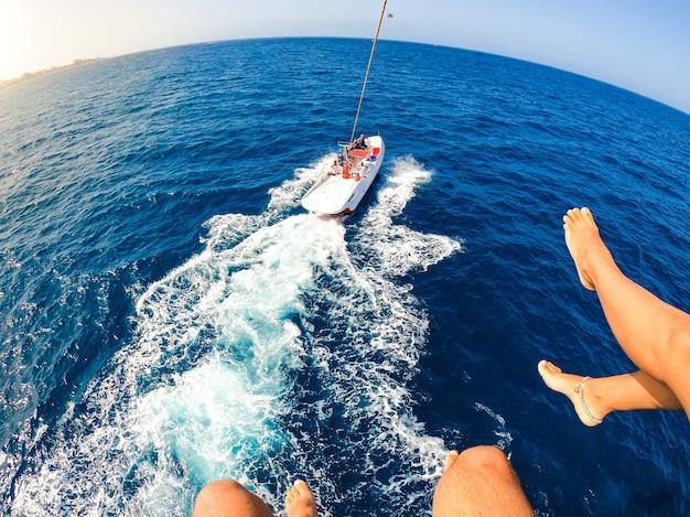Крупным планом и портрет ног двух людей, летящих по воздуху, в то время как лодка тянет их взрослых