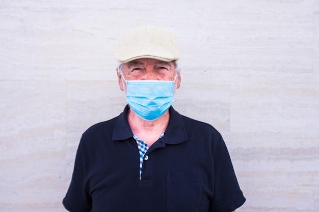 의료 및 수술용 마스크를 쓴 성숙한 남자와 노인의 클로즈업과 초상화 - 카메라를 진지하게 바라보는 노인 - 코로나바이러스, 코비드-19 또는 질병 및 독감 개념