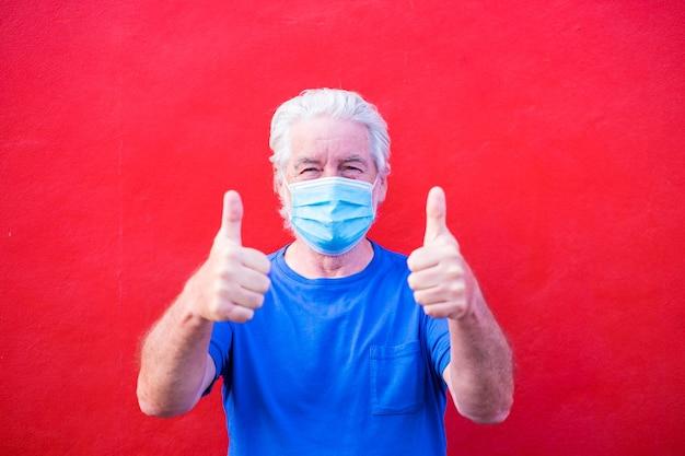 Covid-19または新しいタイプのウイルス、病気、インフルエンザを防ぐために医療用または外科用マスクを着用している成熟した男性または高齢者のクローズアップと肖像画-赤い背景を持つ安全で健康な年金受給者
