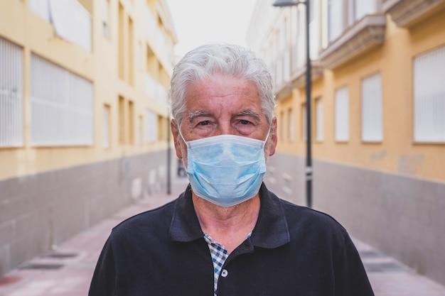 바이러스나 모든 종류의 질병을 예방하는 의료용 마스크를 쓴 성숙한 남자의 클로즈업과 초상화